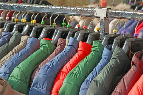 Clothing rack filled with puffy coats of different colors including blue, red, green, and grey.