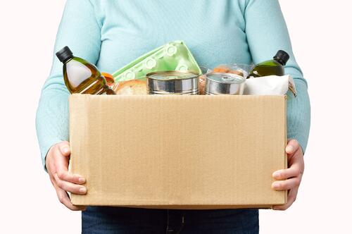 Women in blue sweater holding a cardboard box filled with food and drinks representing food and beverage fulfillment services.
