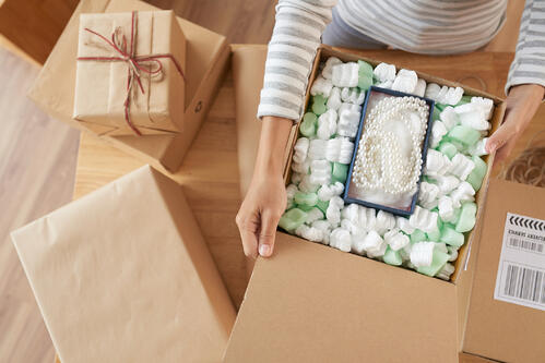 Woman with grey striped shirt opening a package containing a pearl necklace in a padded box.
