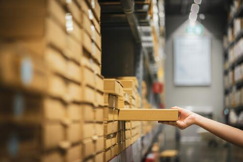 Hand pulling a box off of a shelf with various other boxes in a pick and pack fulfillment warehouse