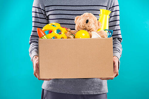 Man in grey striped shirt holding a box of toys including a teddy bear.